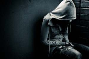 Depressed and potentially suicidal teenager or young person wearing a hoodie. Dark mood photo.